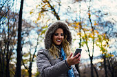 Happy woman in winter park talking mobile phone, sms.