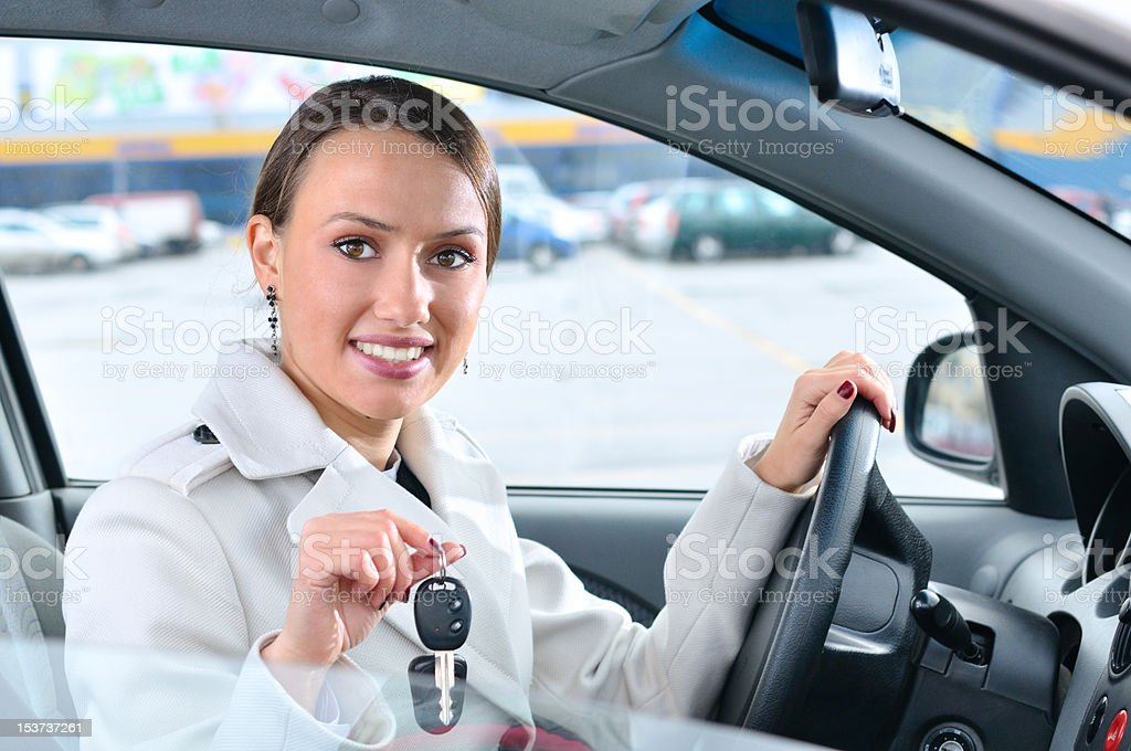 happy woman is showing keys of her new car stock photo