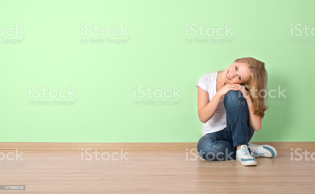 happy  woman is sitting in a room with ablank wall royalty-free stock photo