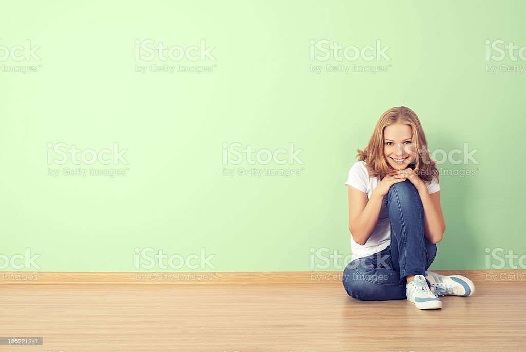 happy  woman is sitting in a room with  blank wall royalty-free stock photo