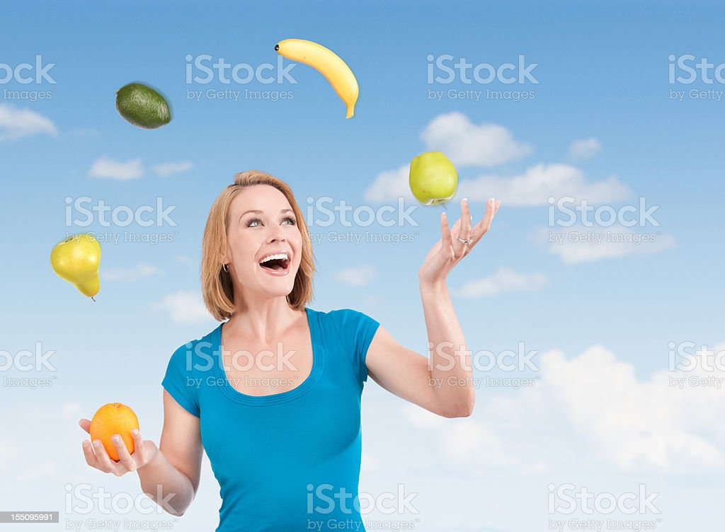 Happy Woman Juggling Produce stock photo