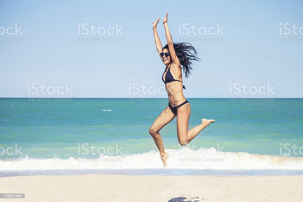 Happy woman jumping on the beach royalty-free stock photo