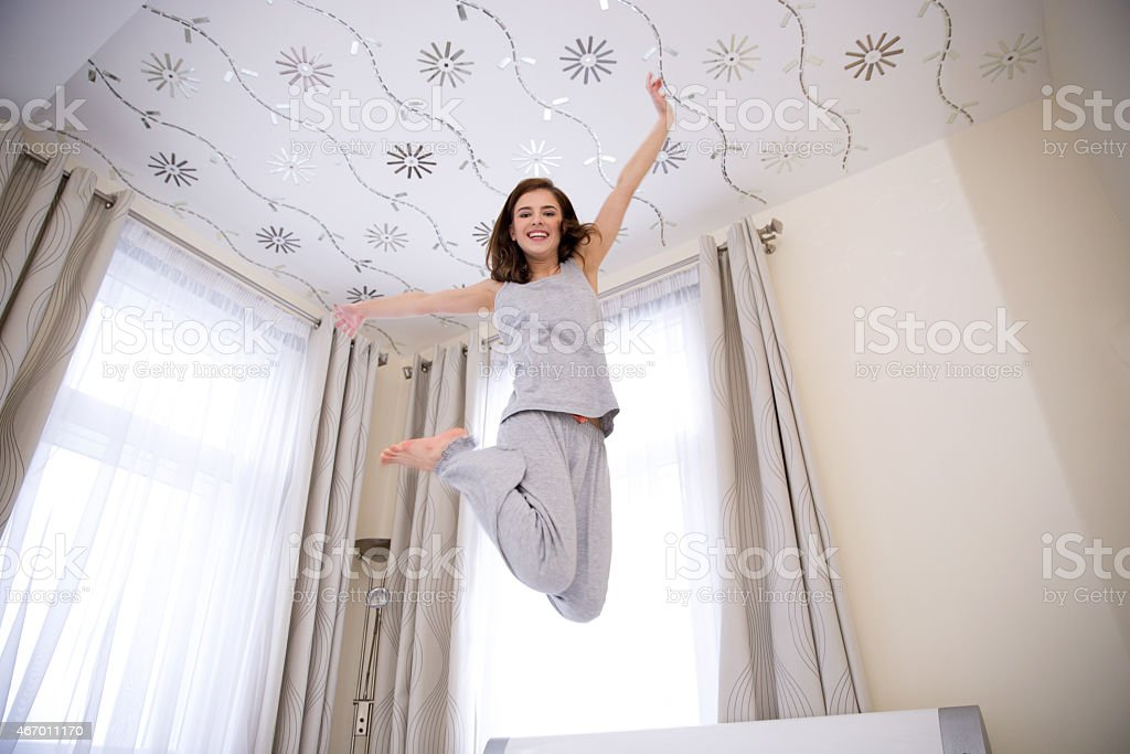 happy woman jumping on the bed stock photo