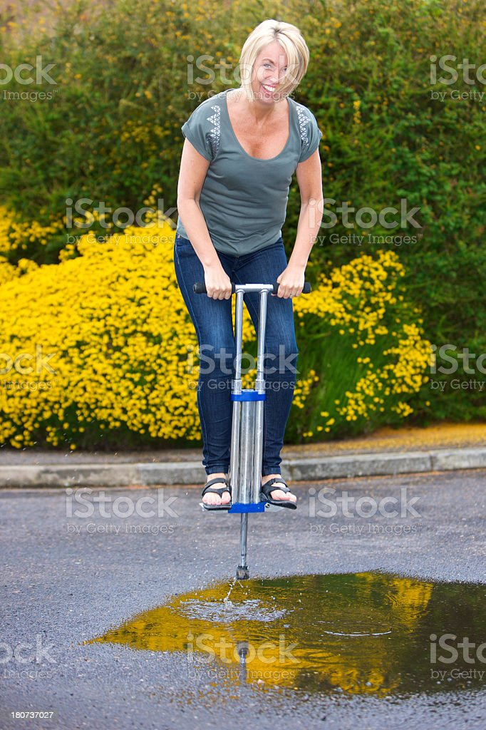 Happy woman jumping through puddle on a Pogo Stick stock photo