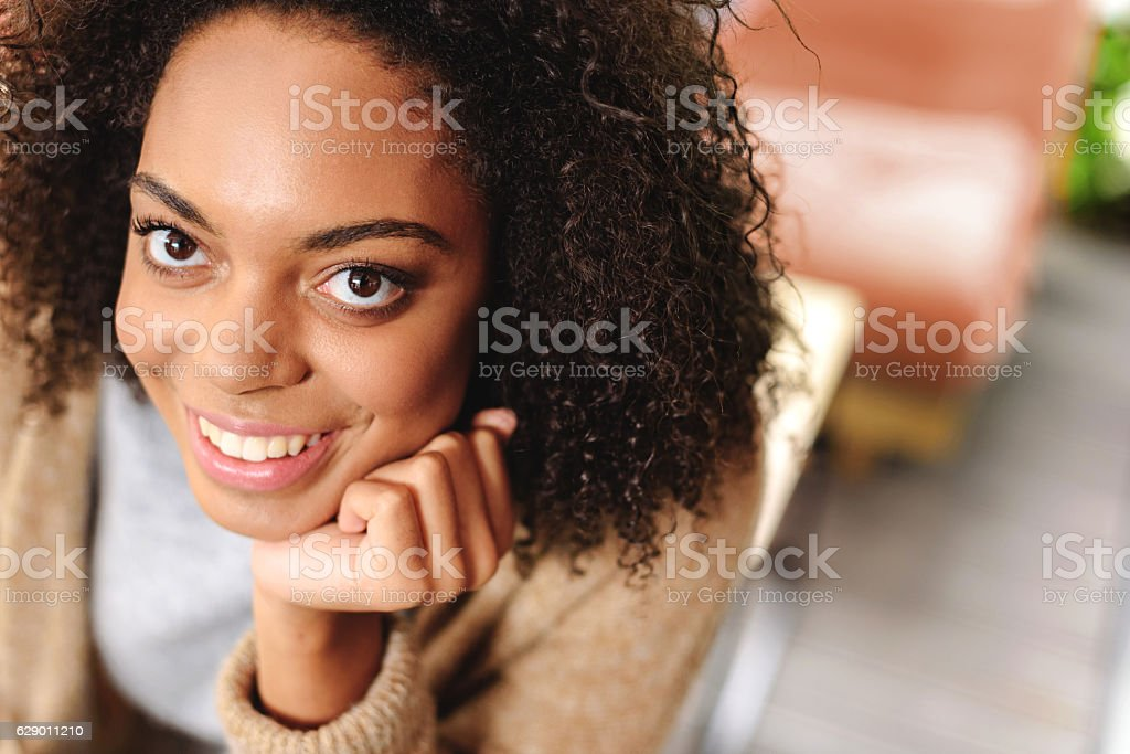 happy woman laughing while sitting indoors stock photo