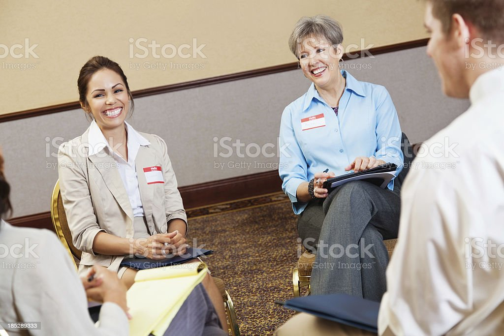 Happy woman laughing with friends in support group stock photo