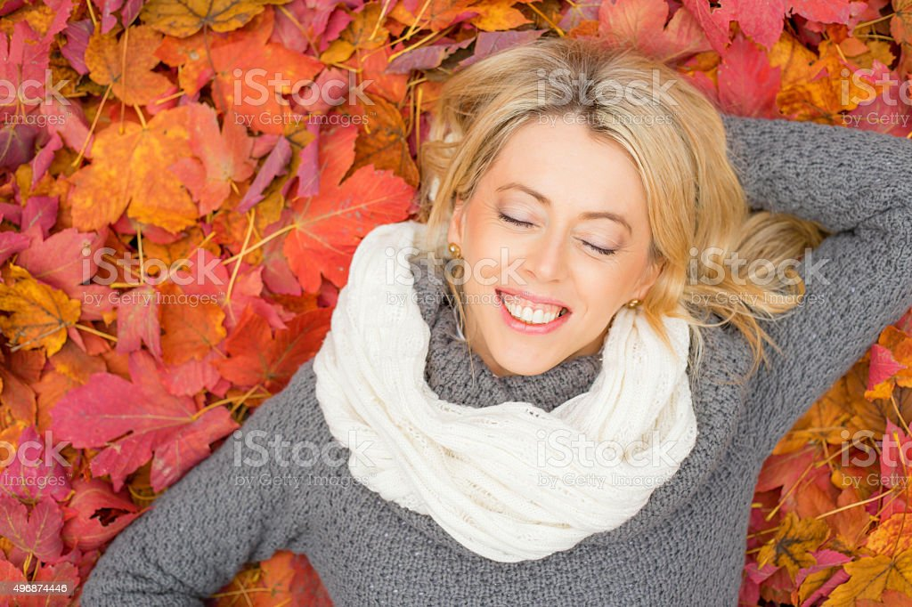 Happy woman laying in leafs and enjoying her time stock photo