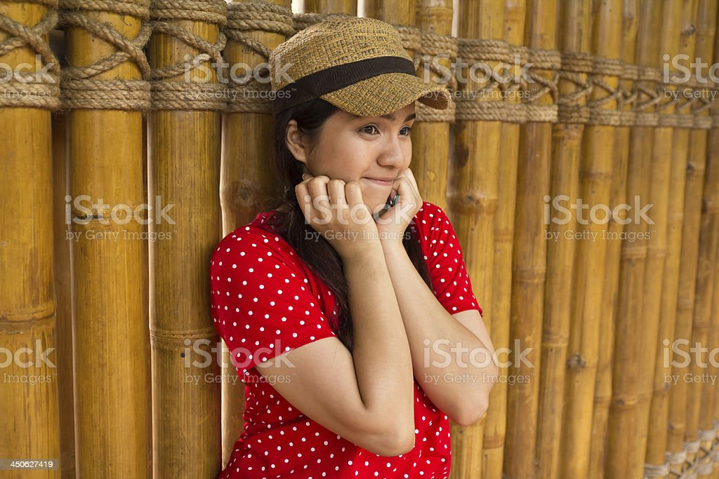 Happy Woman Leaning Against a Bamboo Wall royalty-free stock photo