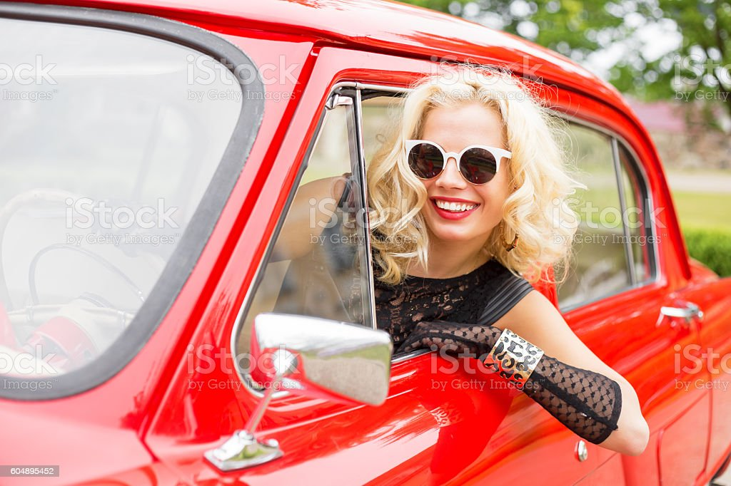 Happy woman leaning out of the car's window stock photo