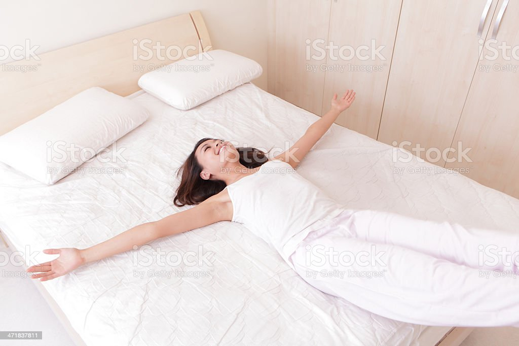 Happy woman lie down on her bed stock photo
