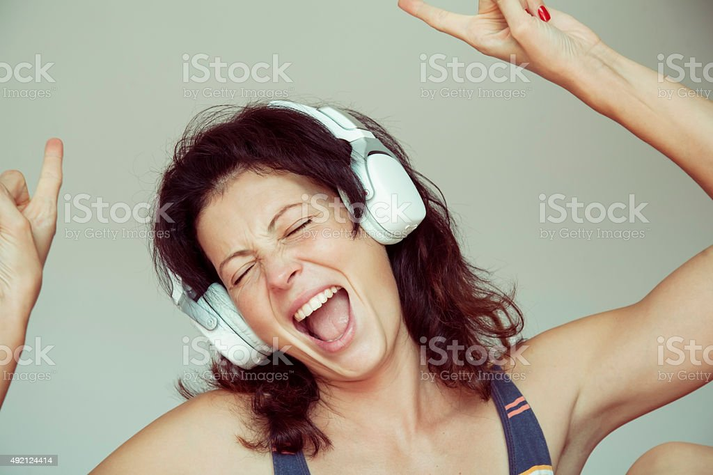 Happy woman listening to music on headphones at home. stock photo