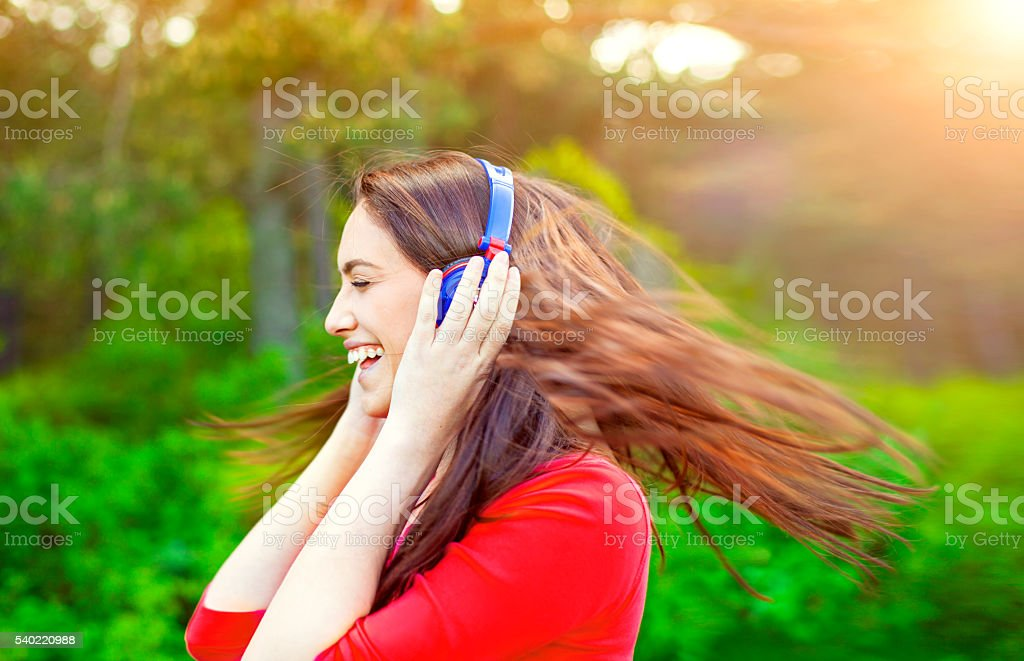 Happy woman listening to the music and waving hair stock photo