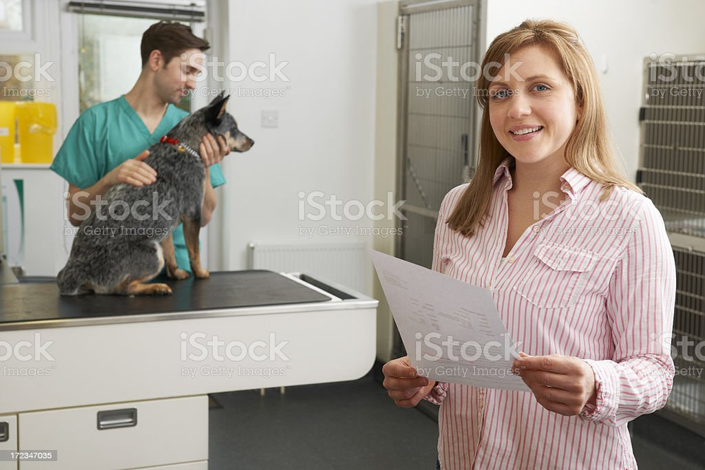 Happy Woman Looking At Bill In Veterinary Surgery royalty-free stock photo