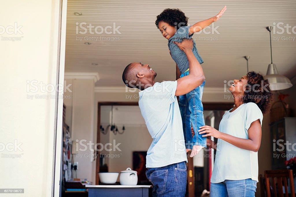 Happy woman looking at man lifting son stock photo