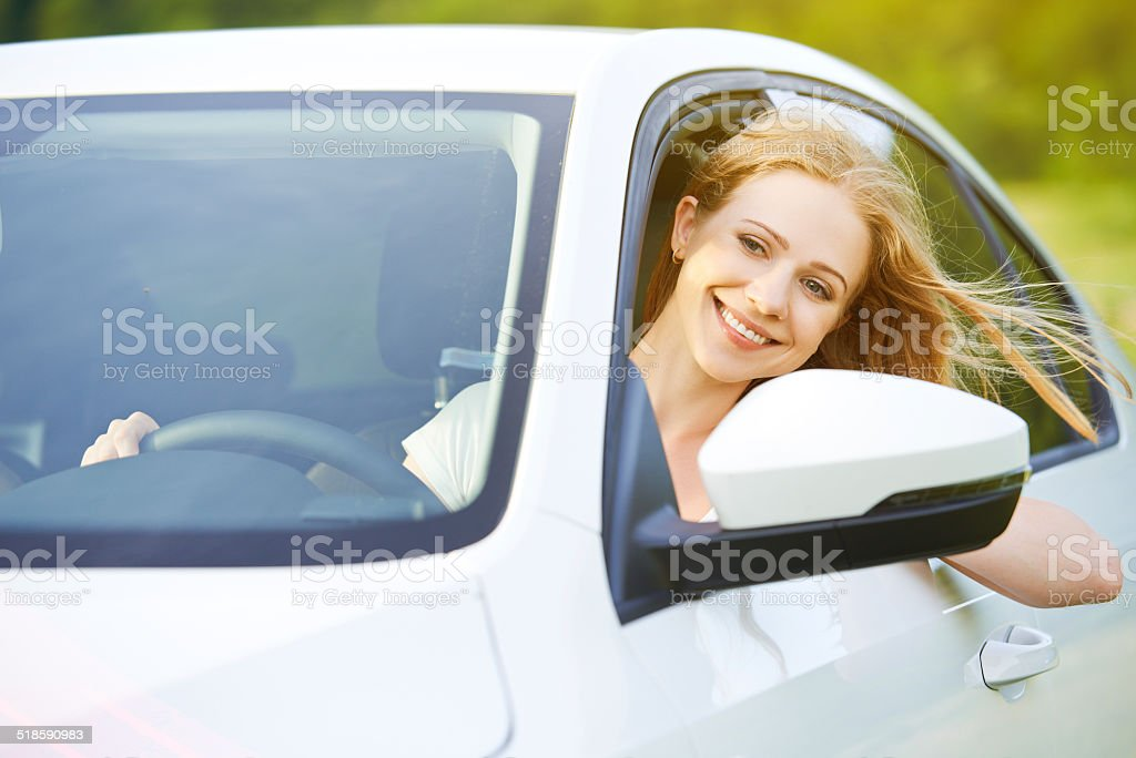 happy woman looks out the car window on nature stock photo