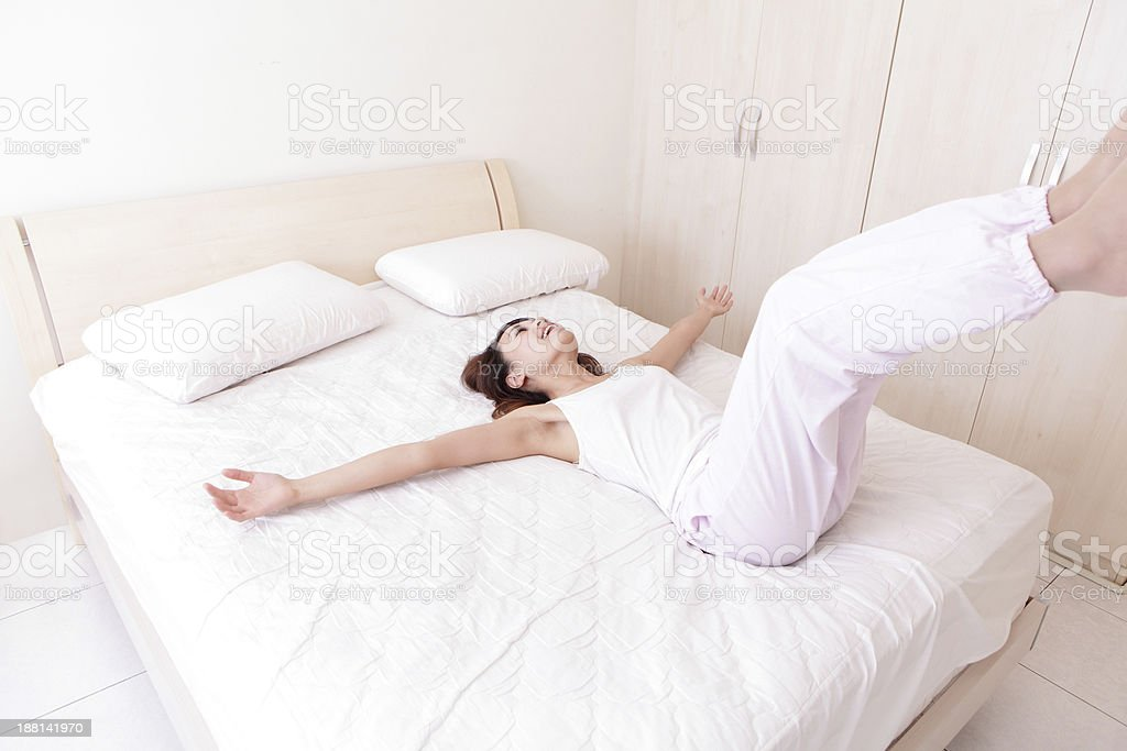 Happy woman lying down on her bed in a white room stock photo
