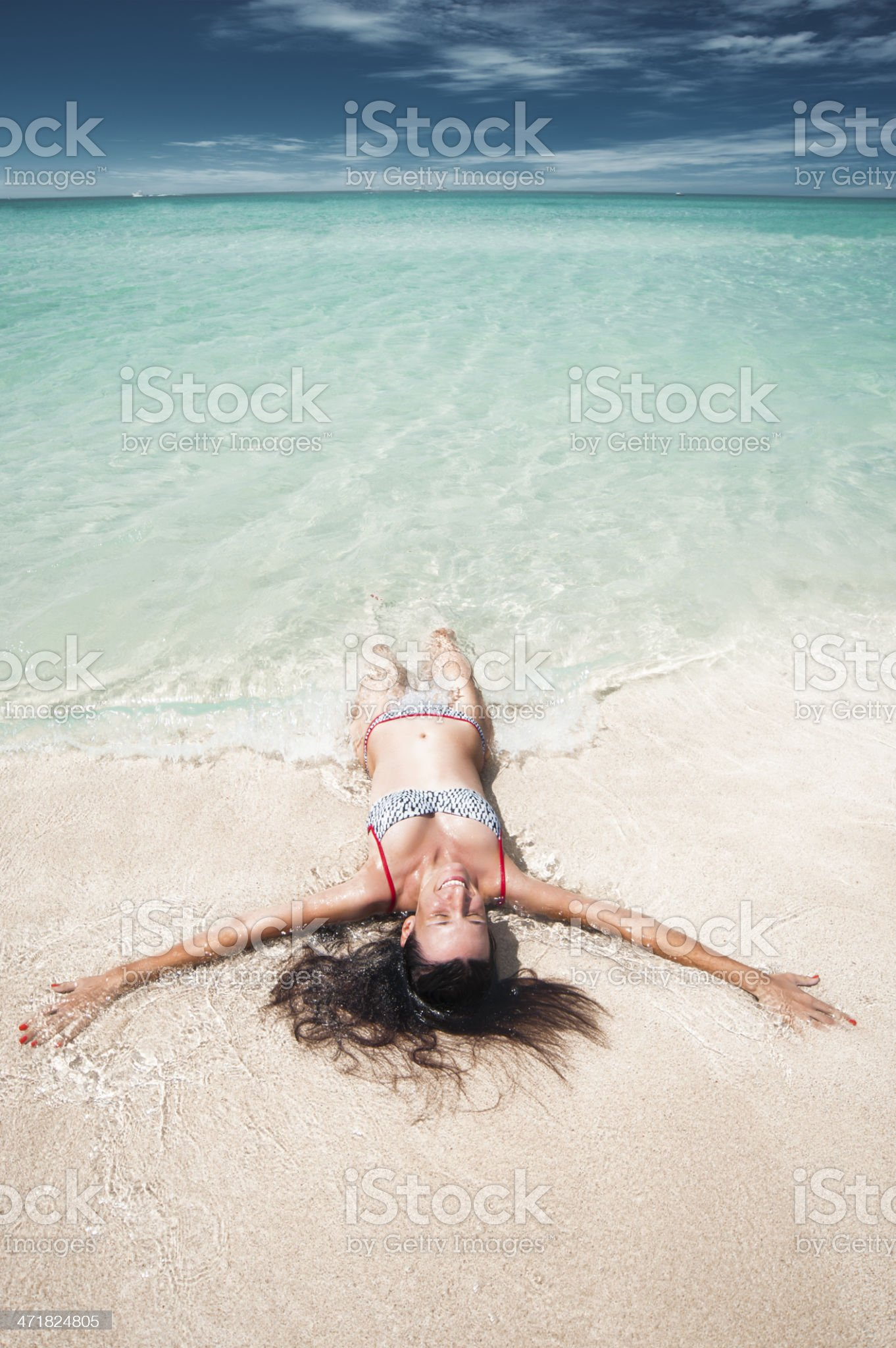 Happy woman lying in water on beautiful beach royalty-free stock photo