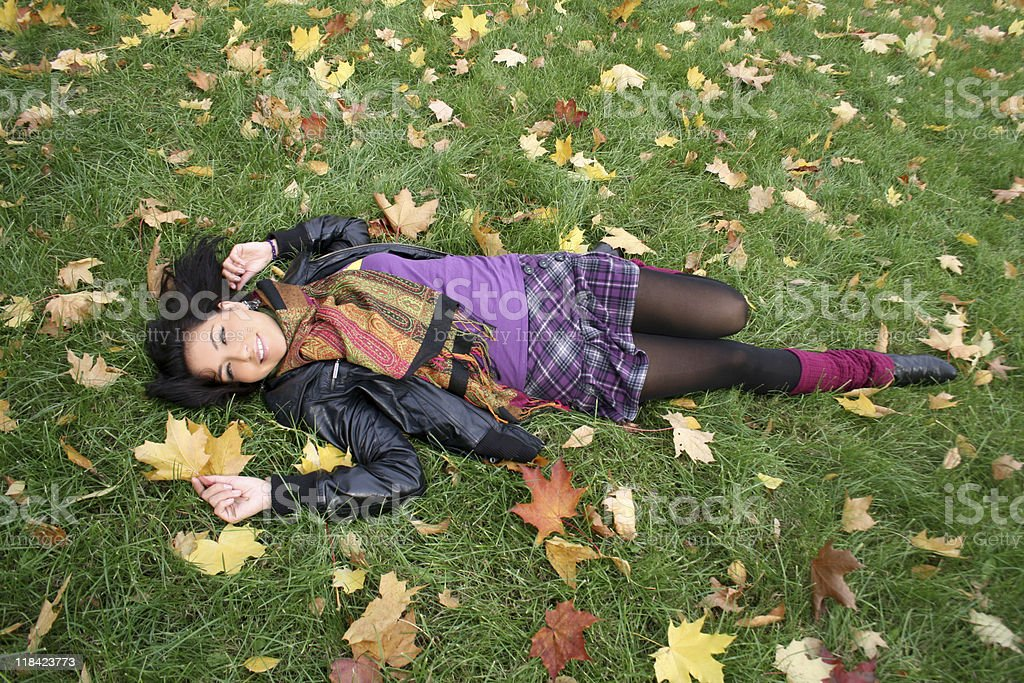 Happy woman lying on a carpet of leaves royalty-free stock photo