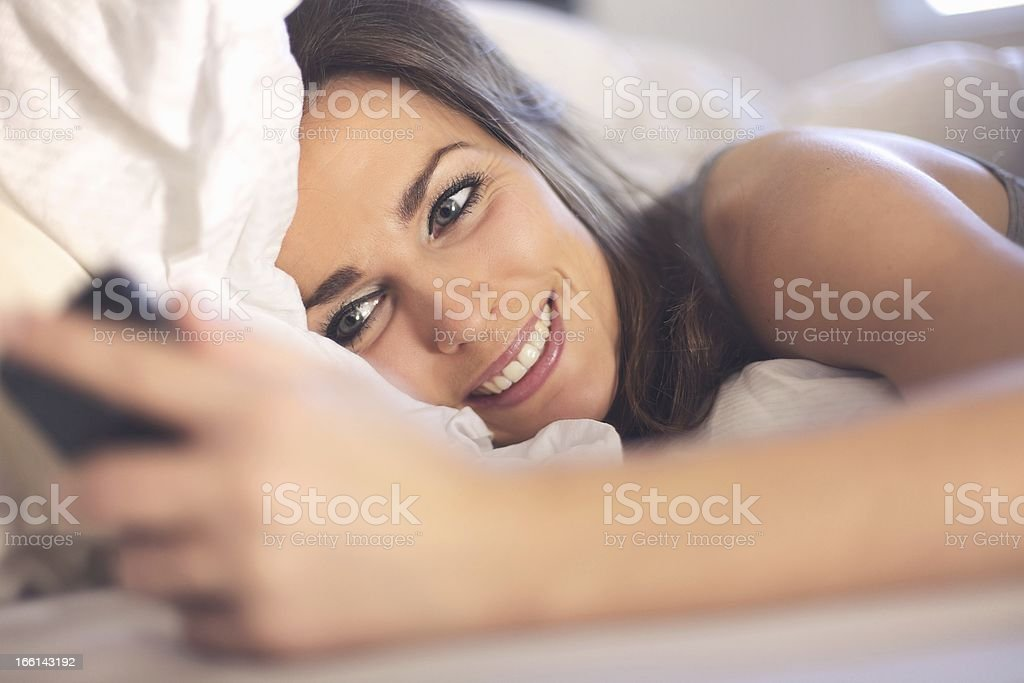 Happy Woman Lying on Bed Reading a Text Message royalty-free stock photo