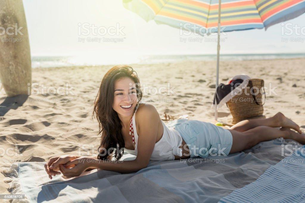 Happy woman lying on blanket at beach stock photo