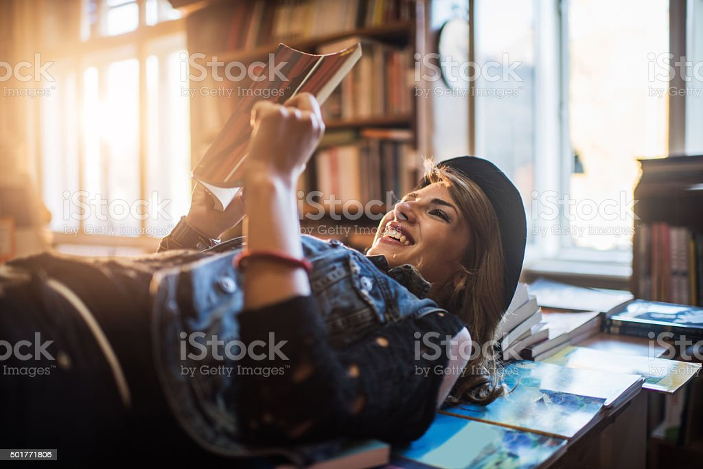 Happy woman lying on books while reading one of it. stock photo