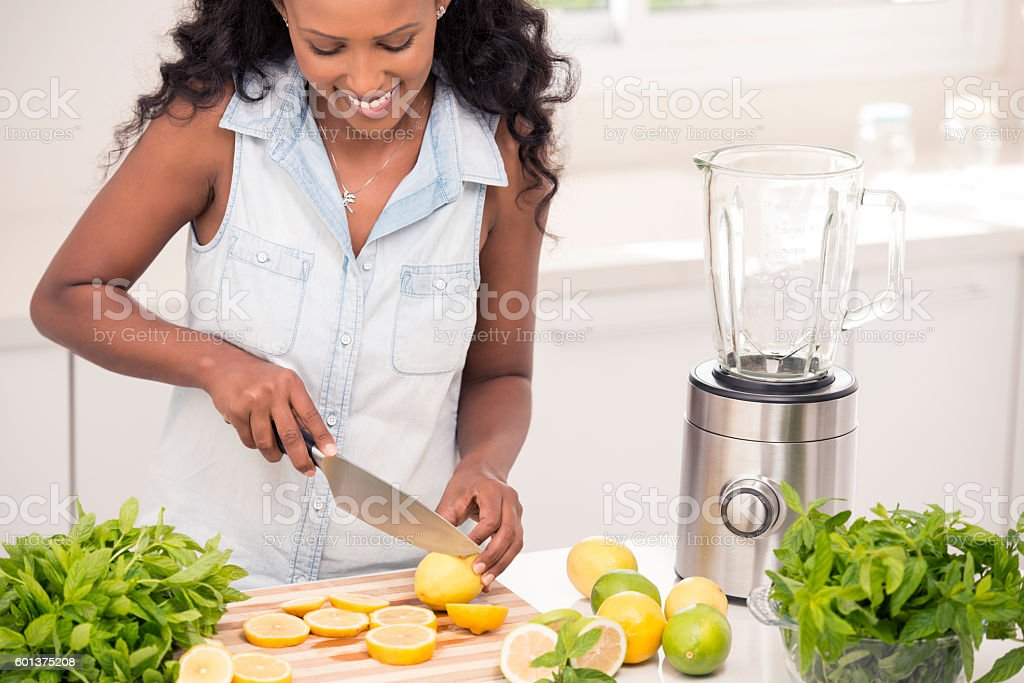 Happy woman making fresh lemonade with mint leaves. stock photo