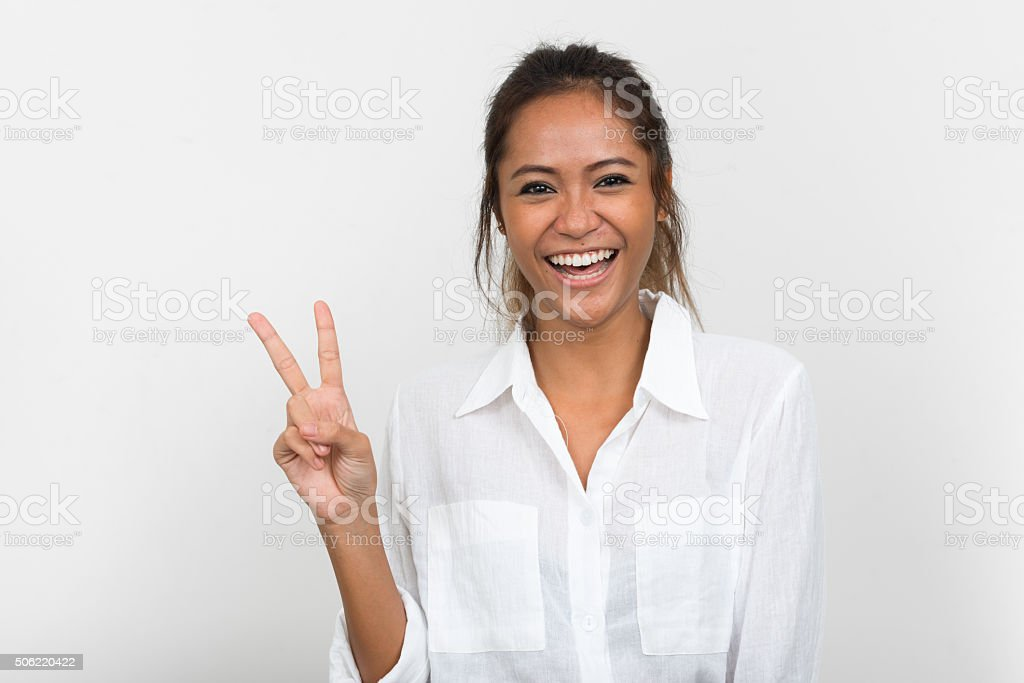Happy woman making peace sign stock photo