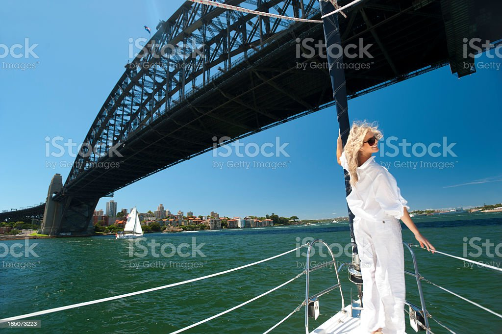 Happy woman on a sailboat Sydney Harbour with bridge stock photo