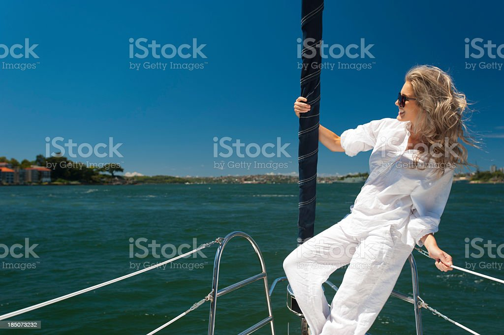 Happy woman on a sailboat with clear blue sky royalty-free stock photo