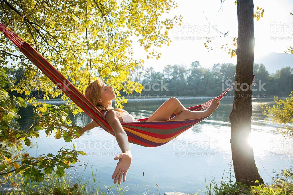 Happy woman on hammock enjoying nature-river stock photo