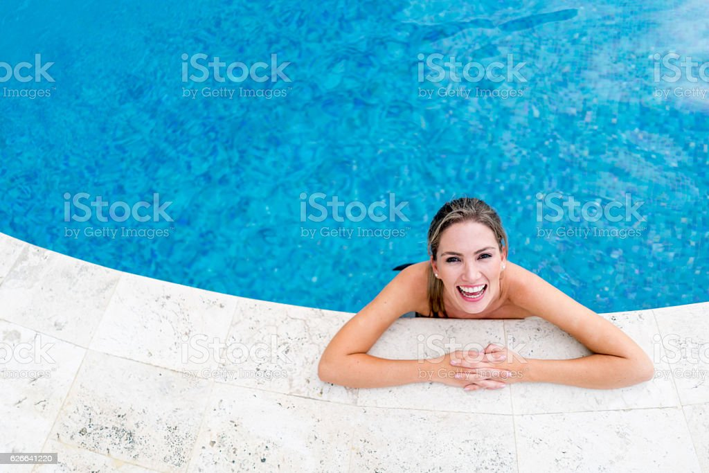 Happy woman on vacations enjoying the pool stock photo