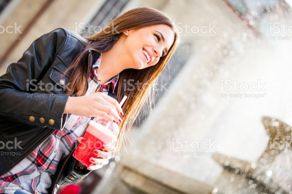 Happy woman outside drinking a smoothie stock photo