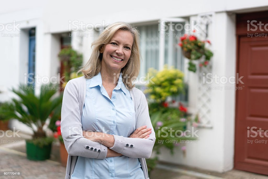 Happy woman outside her house stock photo