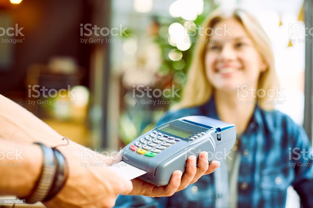 Happy woman paying bill through credit card in cafe stock photo