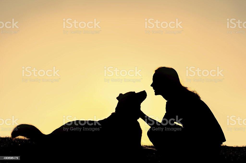 Happy Woman Petting German Shepherd Dog Silhouette stock photo