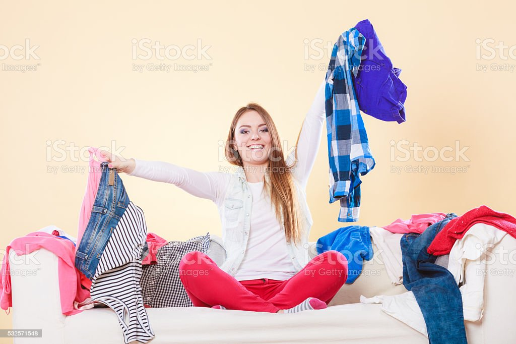 Happy woman picking clothes up in messy room. stock photo