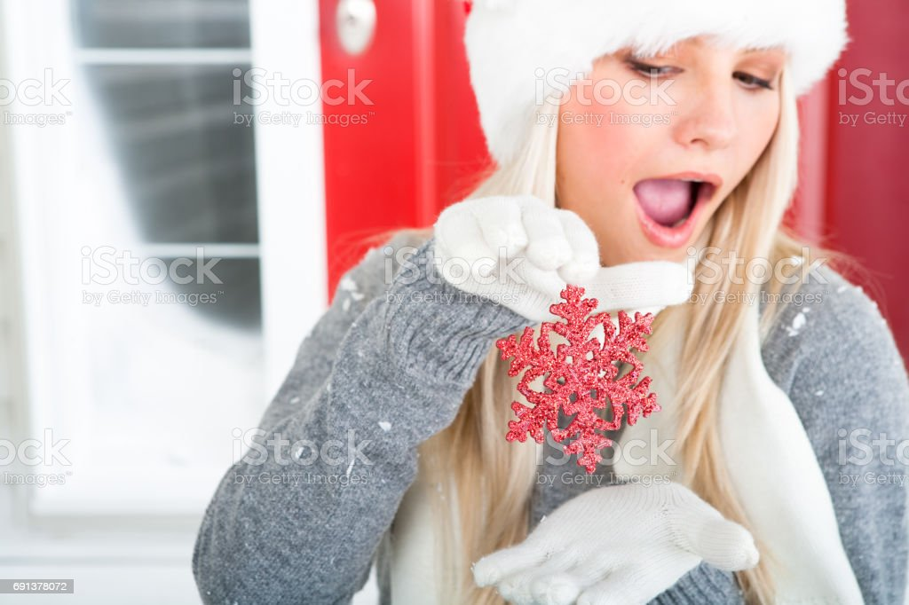 Happy woman playful with Christmas ornament stock photo