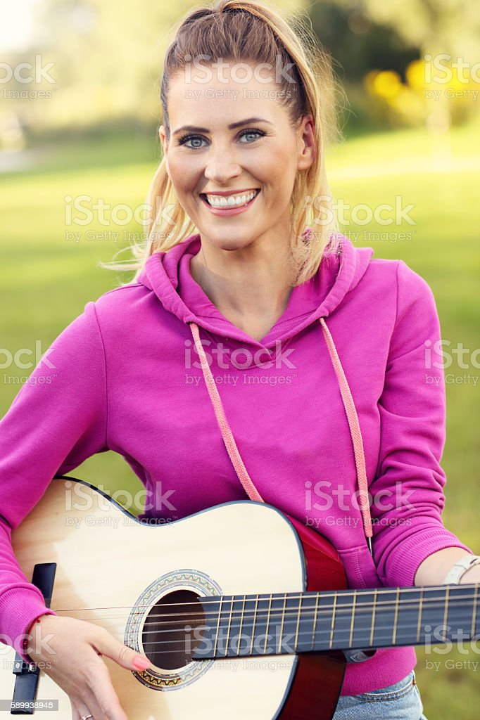 Happy woman playing guitar outdoors stock photo