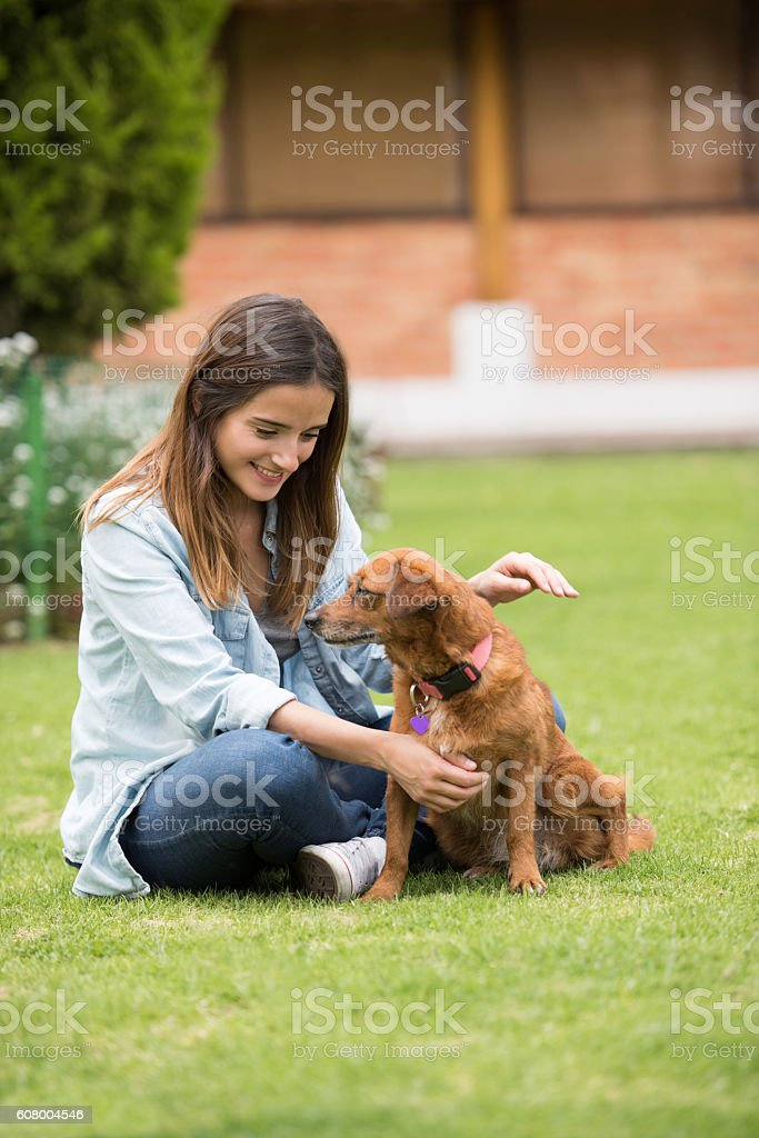 Happy woman playing outdoors with her dog stock photo
