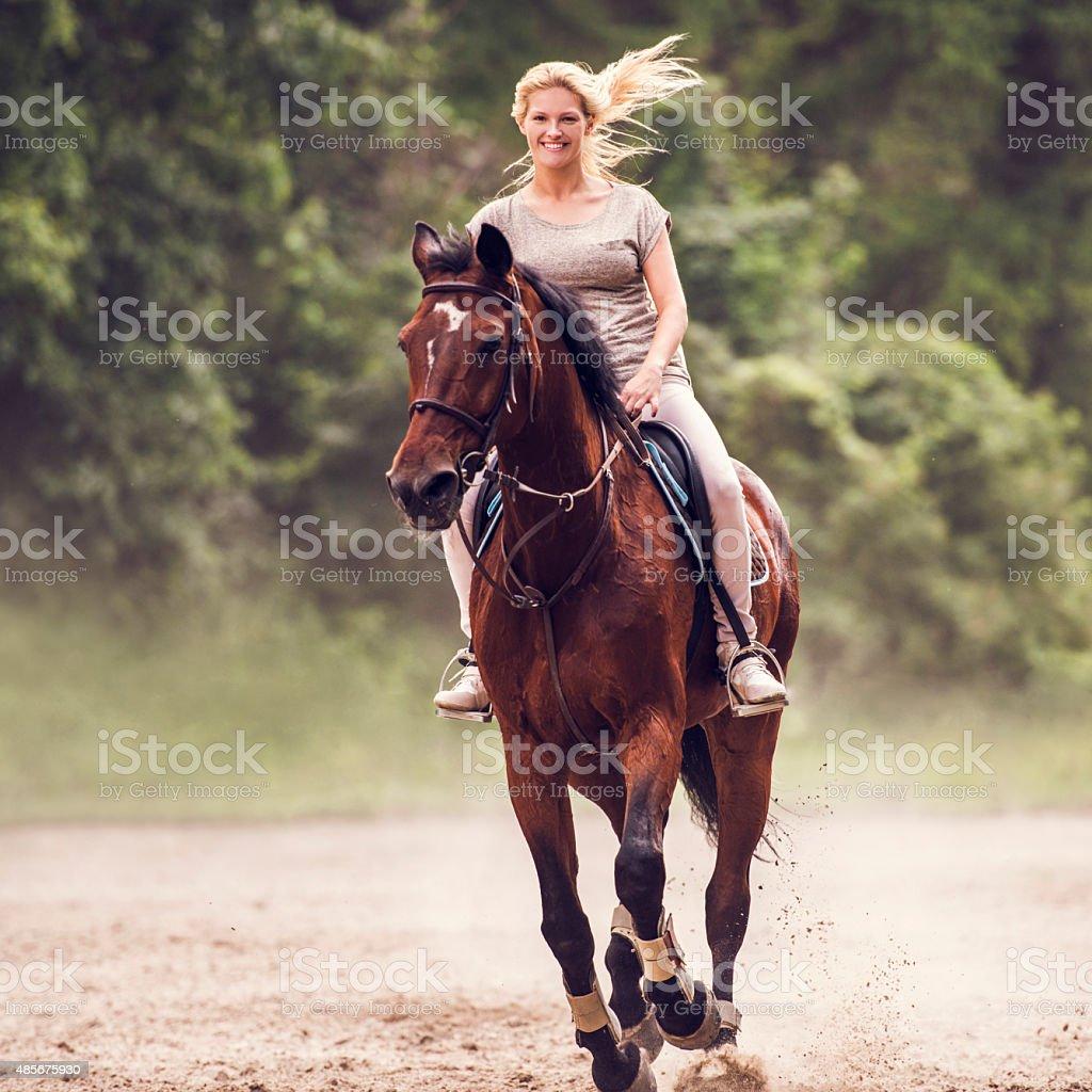 Happy woman practicing horseback riding and looking at camera. stock photo