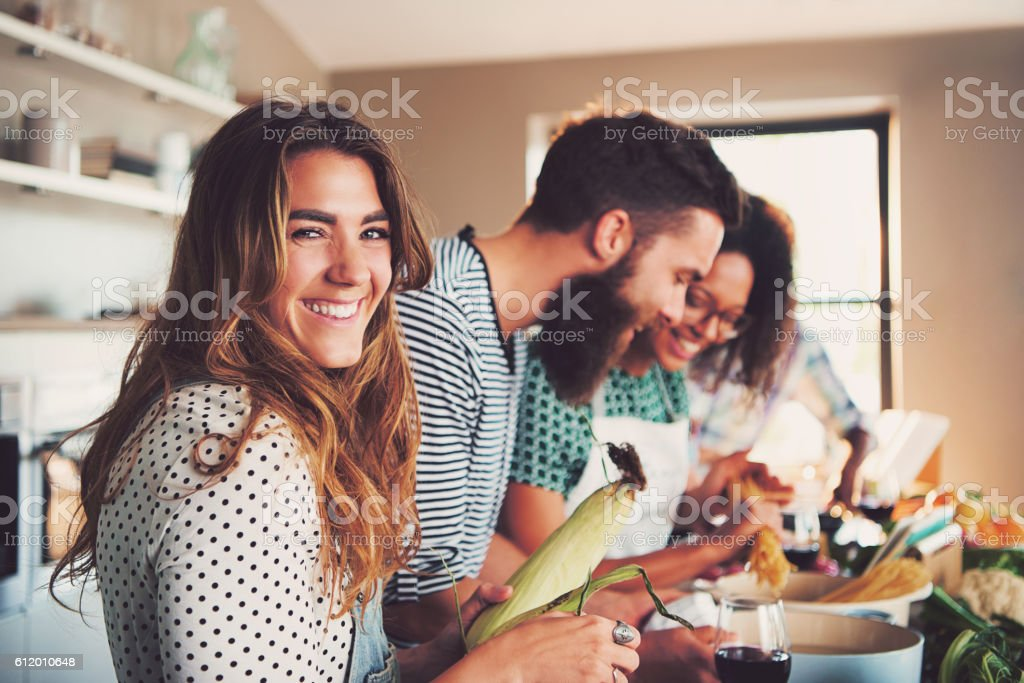 Happy woman preparing food at table in kitchen stock photo