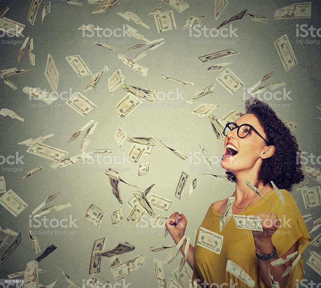 happy woman pumping fists celebrates success under money rain stock photo