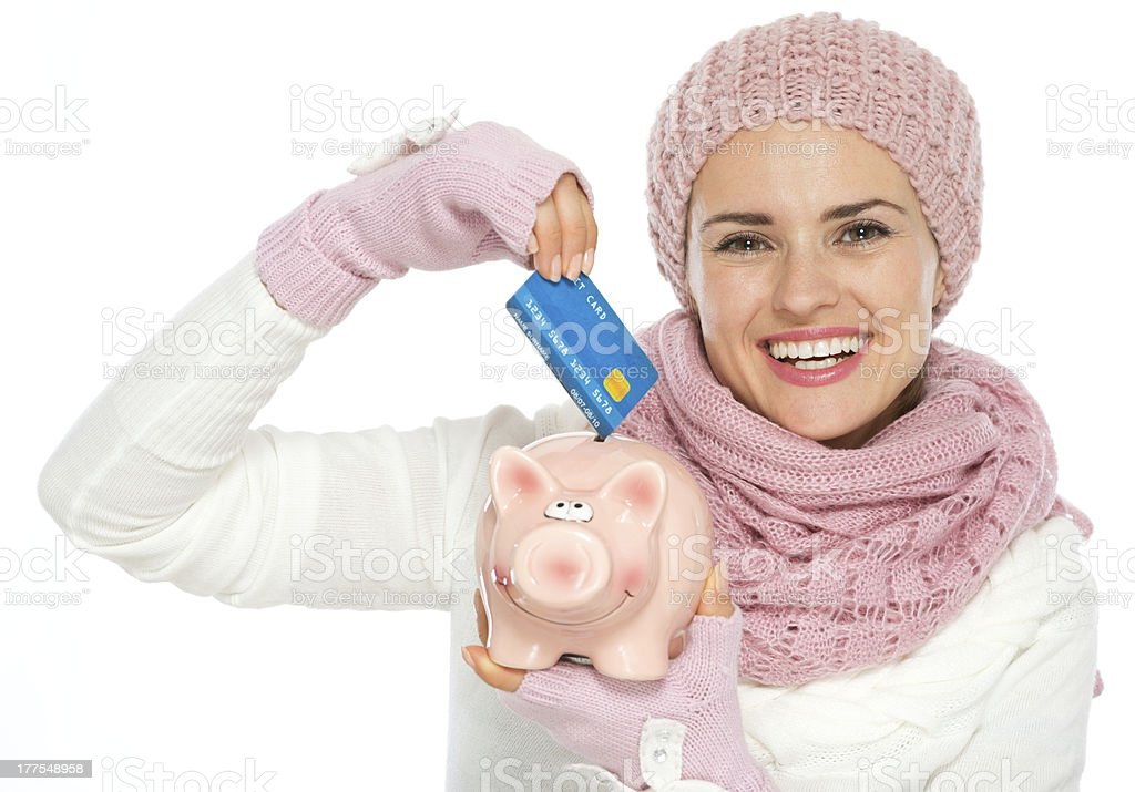 Happy woman putting credit card in piggy bank royalty-free stock photo