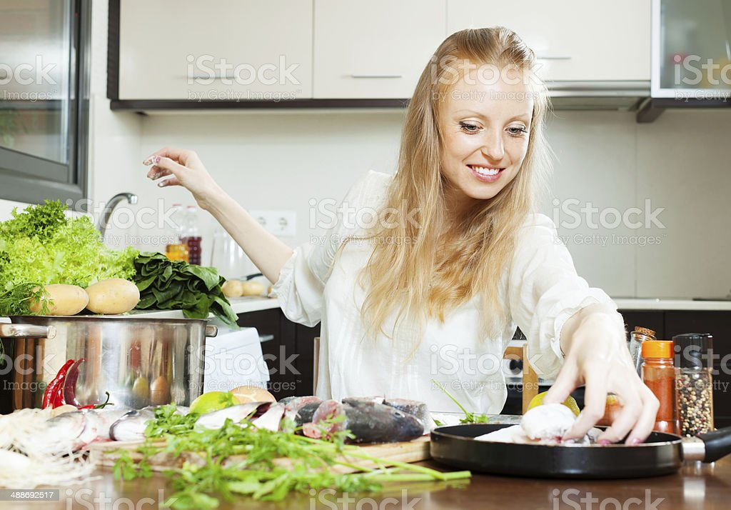 Happy woman putting  fish in flour into frying pan stock photo