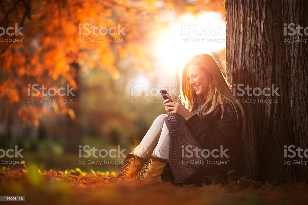 Happy woman reading a text message on mobile phone. stock photo