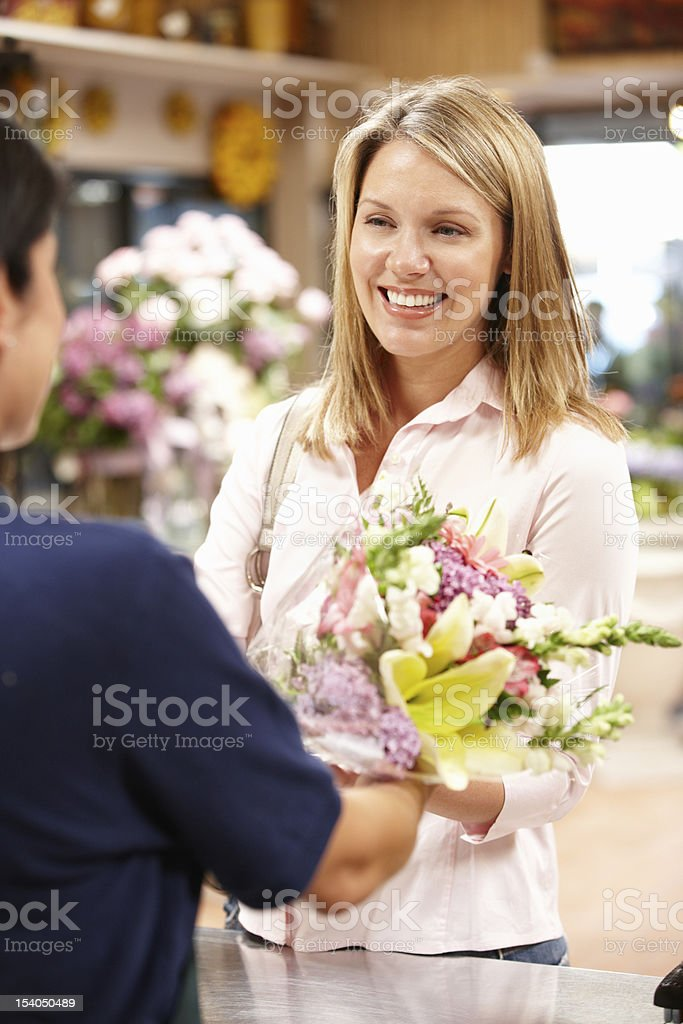 Happy woman receiving a bouquet in a florist royalty-free stock photo