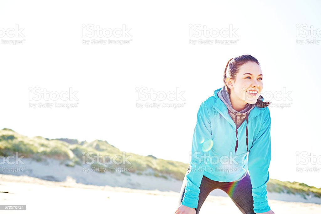 Happy woman relaxing after running workout at beach stock photo
