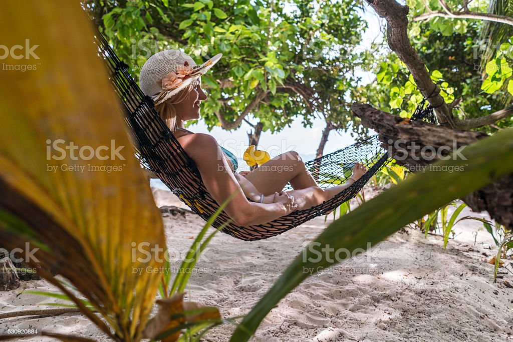 Happy woman relaxing in hammock on the beach. stock photo