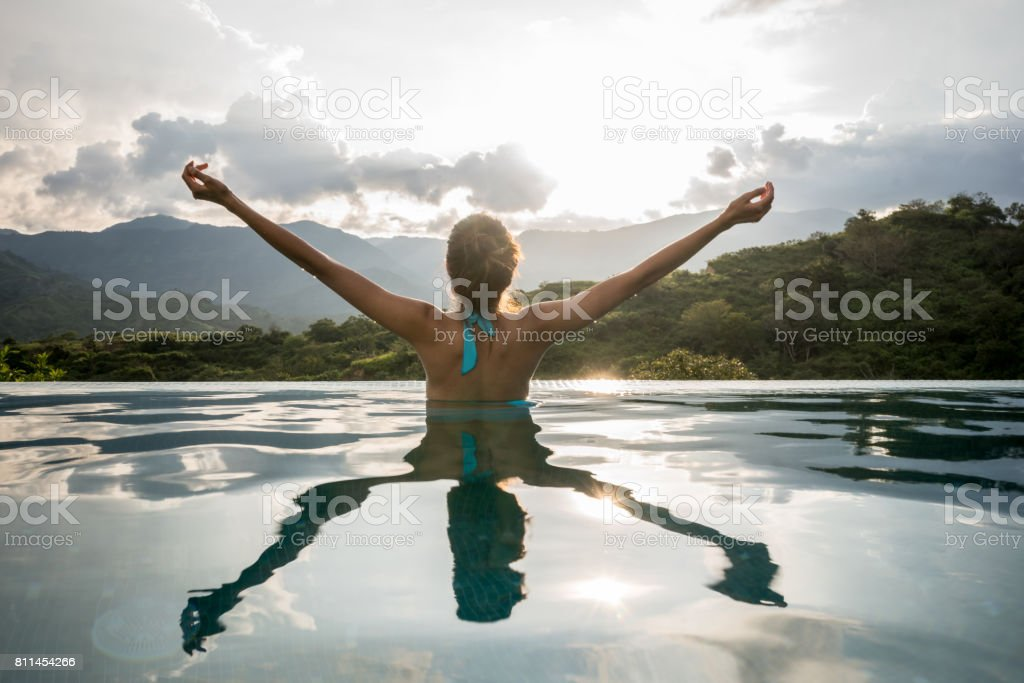 Happy woman relaxing in the pool with arms up stock photo