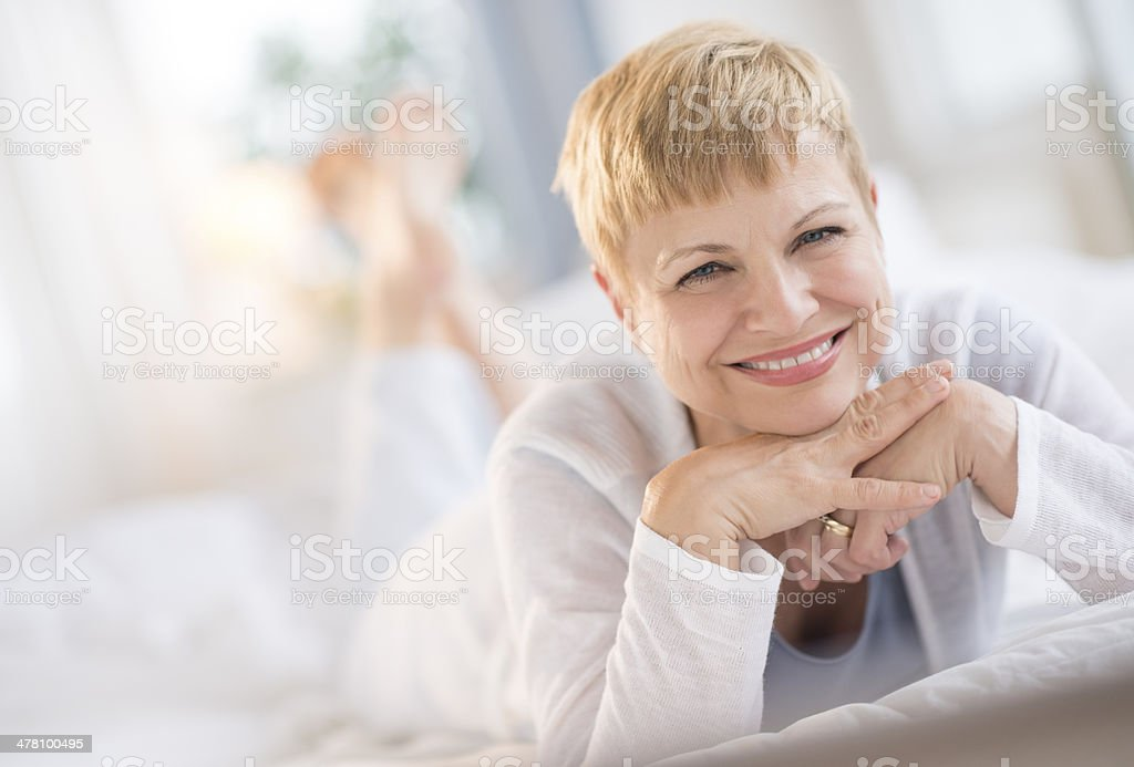 Happy Woman Resting Chin On Hands While Lying In Bed stock photo
